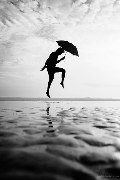Abilash Thankan jumping with an umbrella at Azhimala beach in Trivandrum, Kerala, India